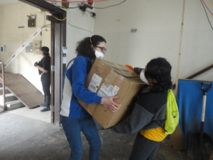 Photo by Isioma Ononye  Queens College students Grace Magee and Bridgette Garcia help move boxes at St. Gertrude's church in Far Rockaway.