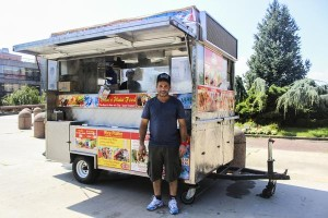 Photo by Amanda Goldstein A worker of Shah's Halal Food stands in front of a new dining option for Queens College students.